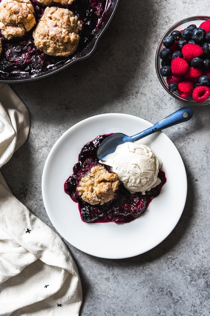 White plate with mixed berry cobbler and ice cream.