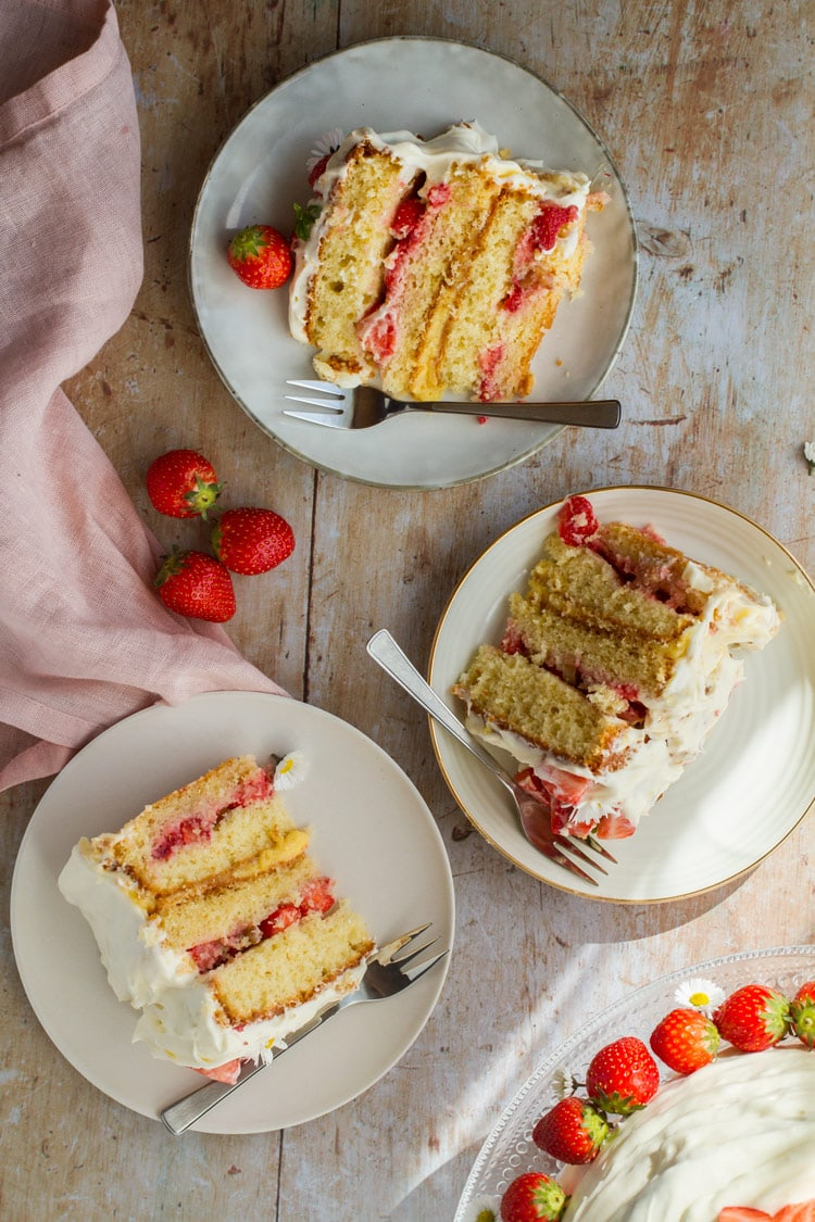 Three slices of strawberry and lemon curd layer cake.