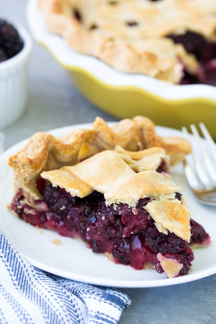 Slice of blackberry pie on a white plate.