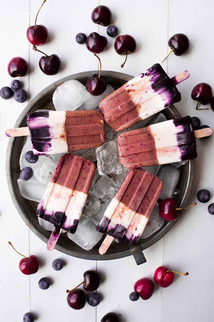 5 popsicles on a tray of ice.