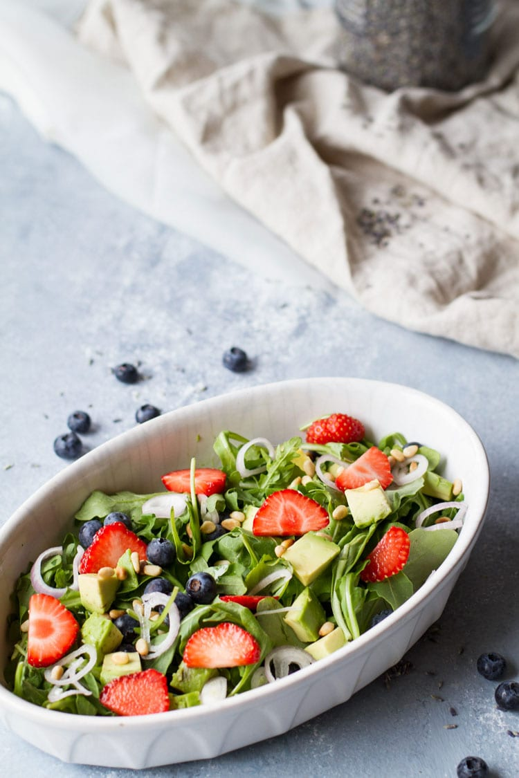 Large bowl with arugula, strawberries and blueberries.