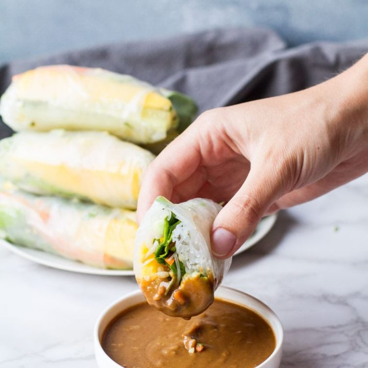 Hand holding a sliced open summer roll dipped in peanut sauce.