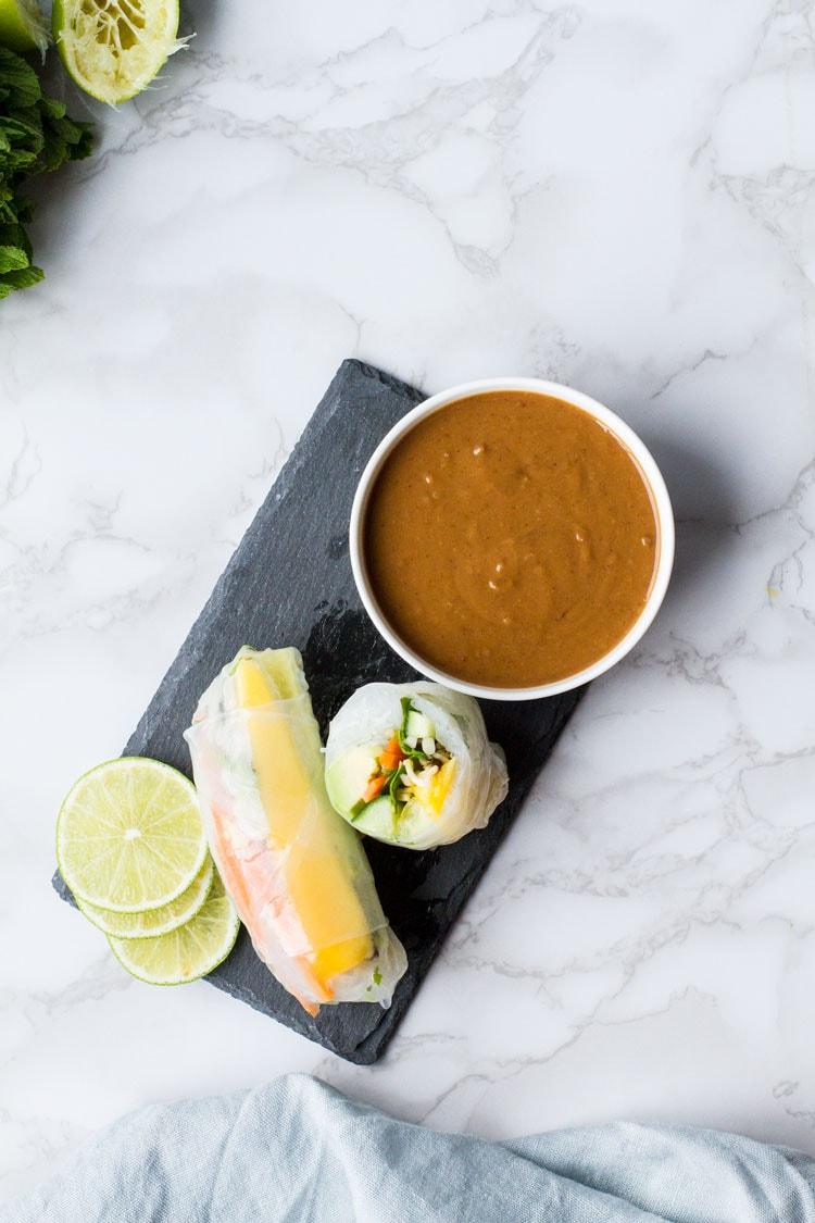 Summer rolls and peanut sauce on a slate.