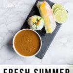 Summer rolls and peanut sauce on a slate. Pinterest pin.