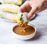 Hand holding a sliced open summer roll dipped in peanut sauce. Pinterest pin.