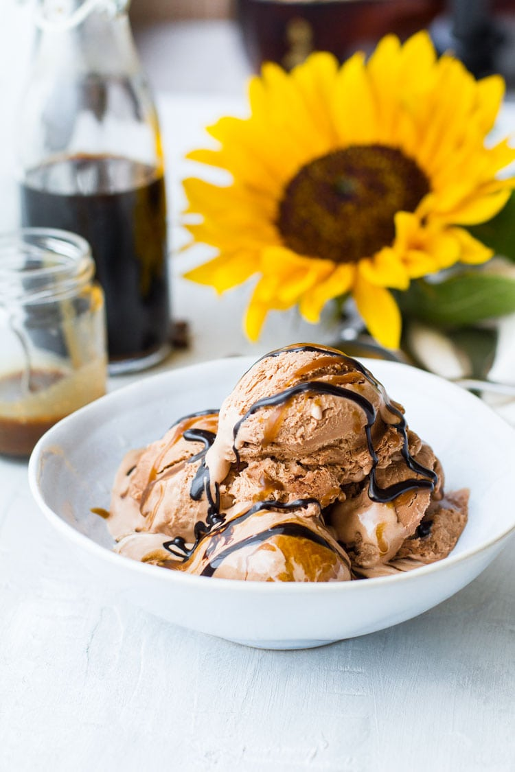 Several chocolate ice cream scoops in a bowl with caramel and chocolate sauce.