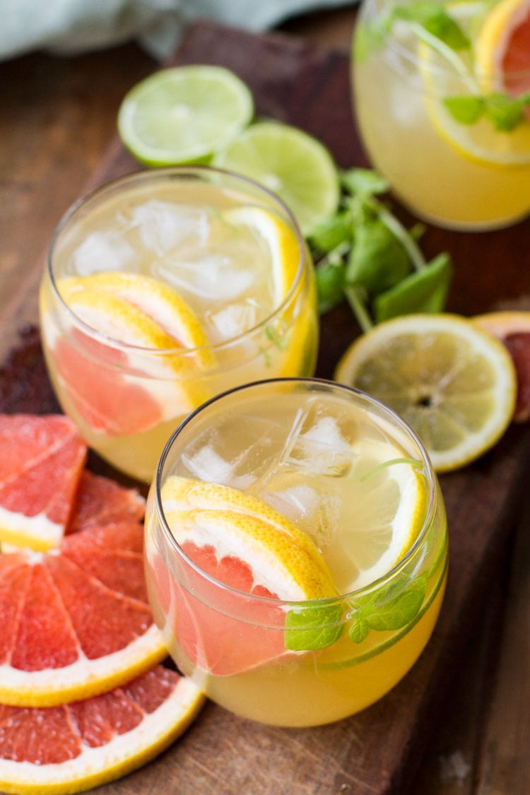 Two glasses with iced tea, citrus slices and mint leaves.