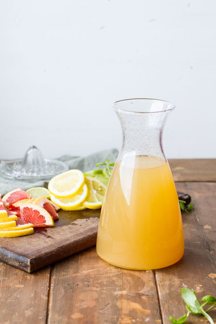 A carafe with iced green tea. Sliced citrus in the background.