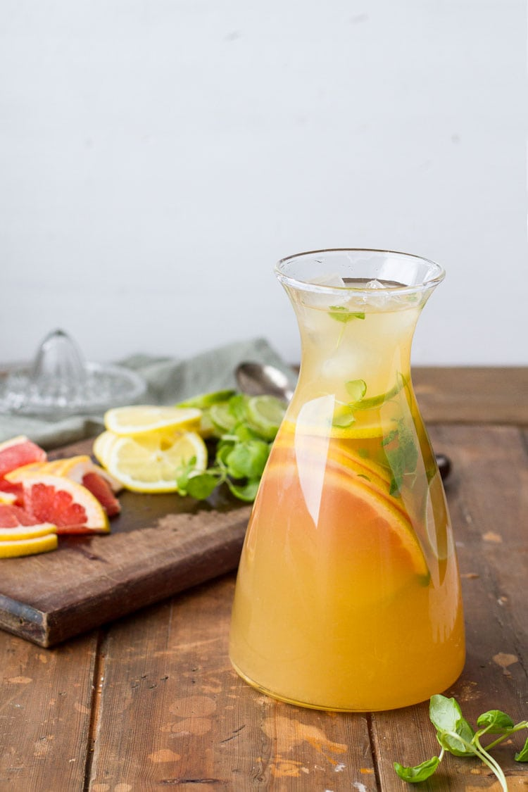 A carafe with iced green tea and sliced citrus fruit.