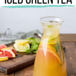 A carafe with iced green tea and sliced citrus fruit. Pinterest pin.