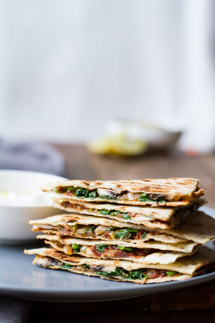 Stack of cut open spinach mushroom quesadilla.