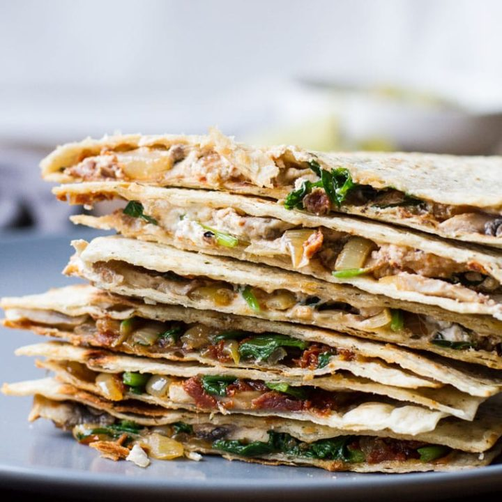 Stack of cut open spinach mushroom quesadilla. Close-up.