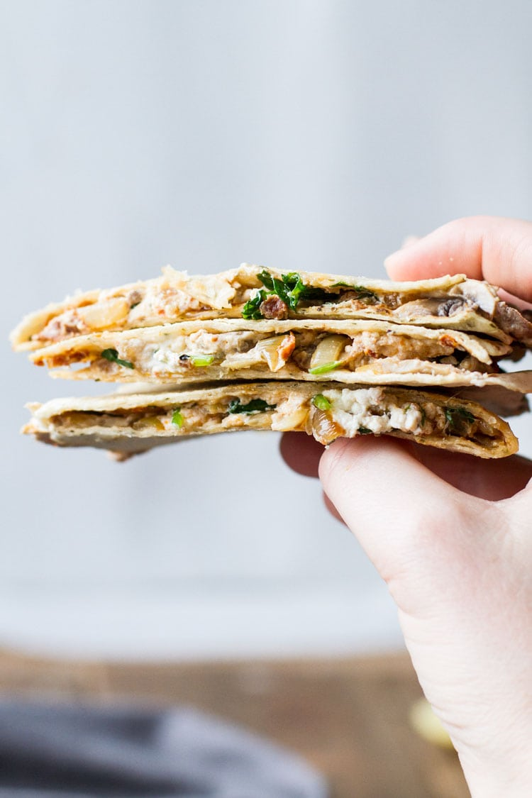 Hand holding three pieces of quesadilla in a stack.