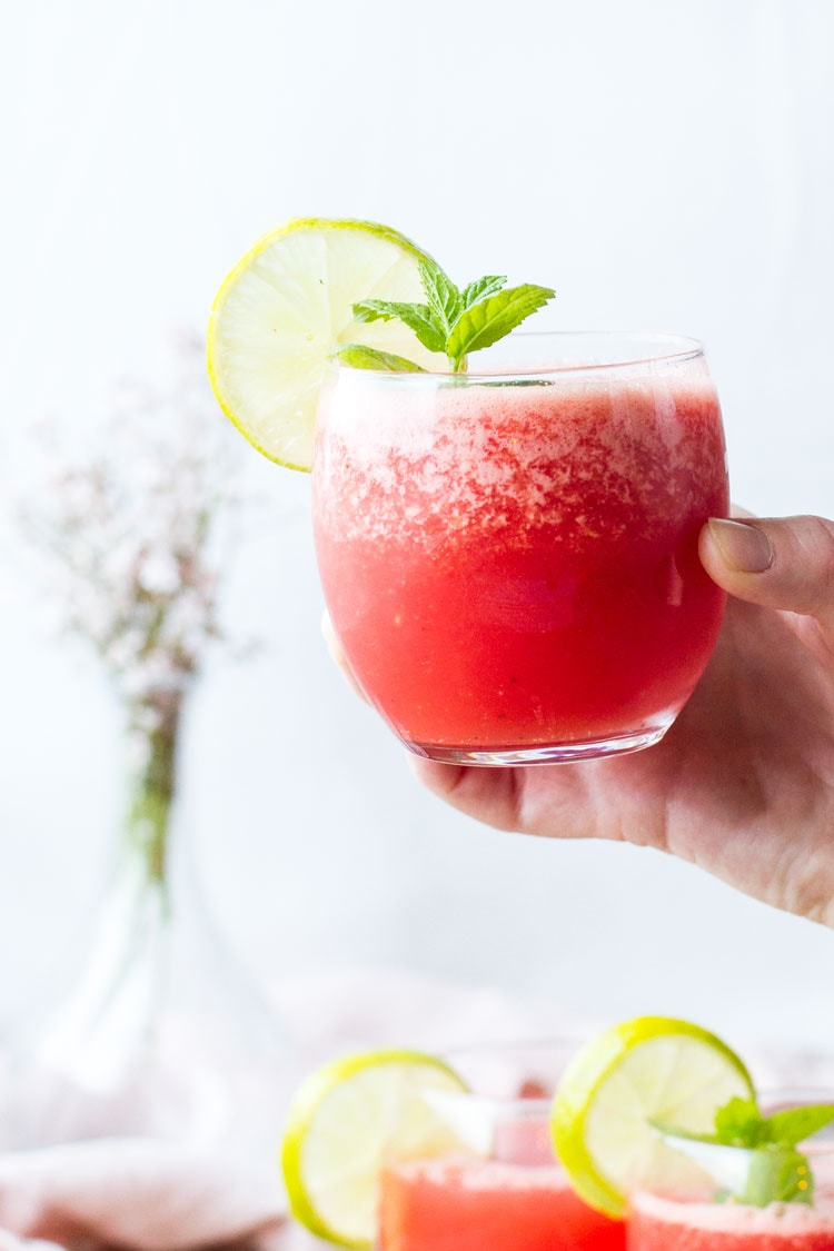 Hand holding a glass of watermelon limeade, garnised with lime and mint.