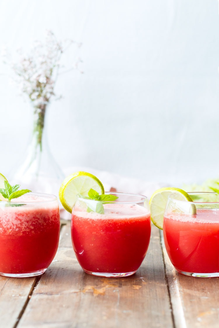 Three round glasses with watermelon limeade, lime wedges and mint on a row.