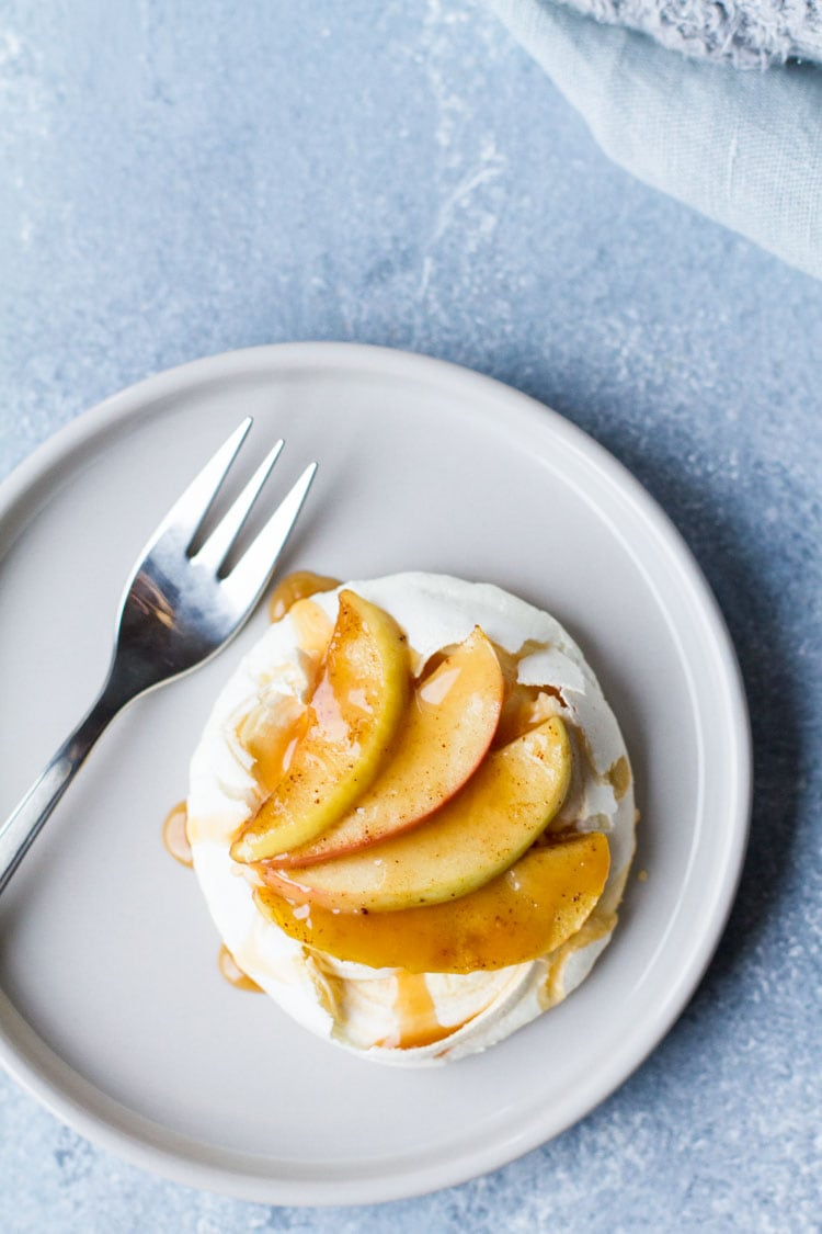 One salted caramel apple mini pavlova on a small plate with a fork.