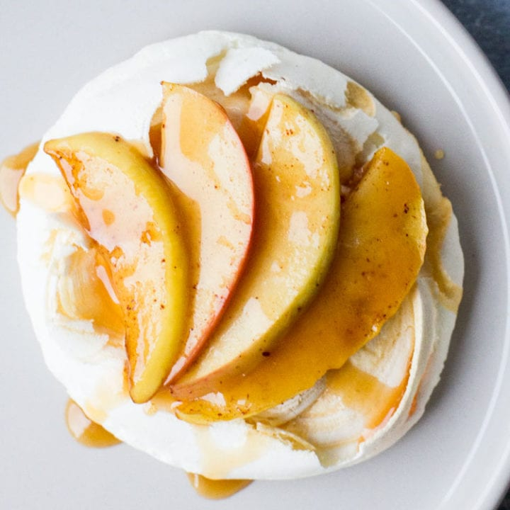 Close-up of one mini pavlova with sliced apples and caramel.