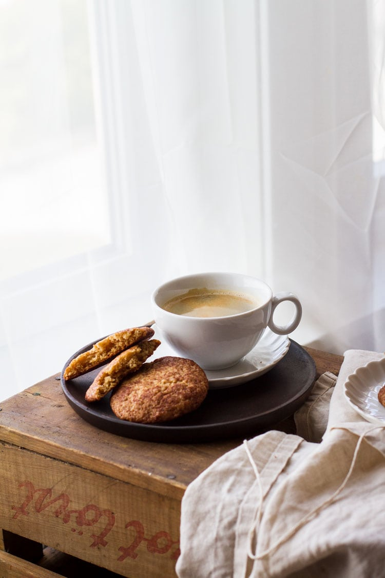 Cookies and coffee on a wooden plate on a wooden table, next to a window with see through white curtains.