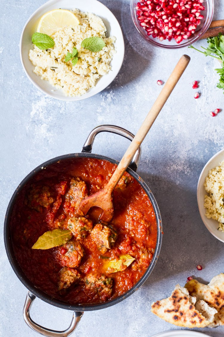 Saucepan with kofta meatballs in tomato sauce. Couscous and pomegranate on the side.