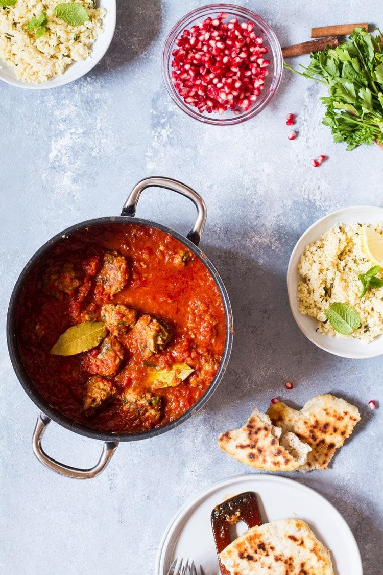 Casserole with kofta meatballs in tomato sauce. Torn pita bread, couscous and pomegranate around.