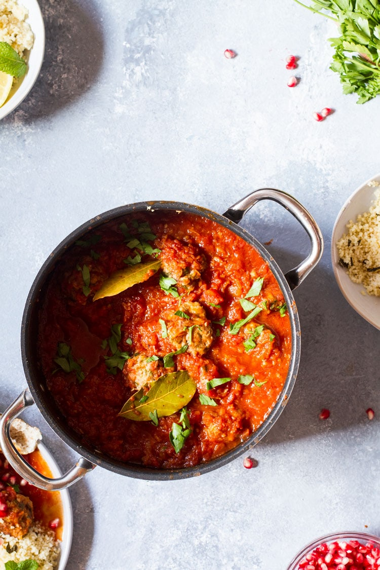 Large saucepan with meatballs, parsley and tomato sauce.