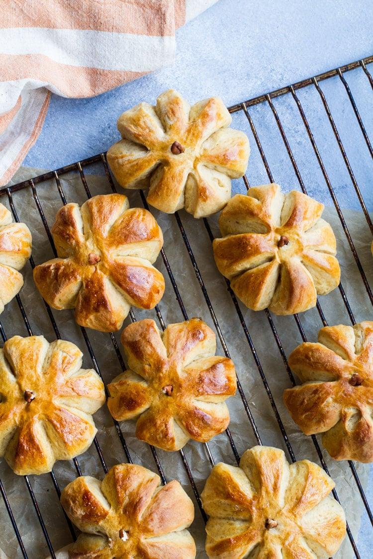 Pumpkin shaped sweet rolls on a cooling rack.