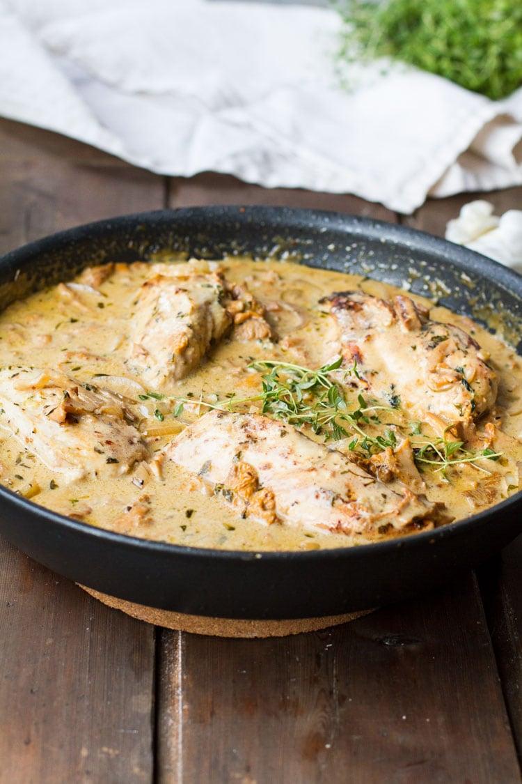 Chicken and mustard cream sauce in a skillet.