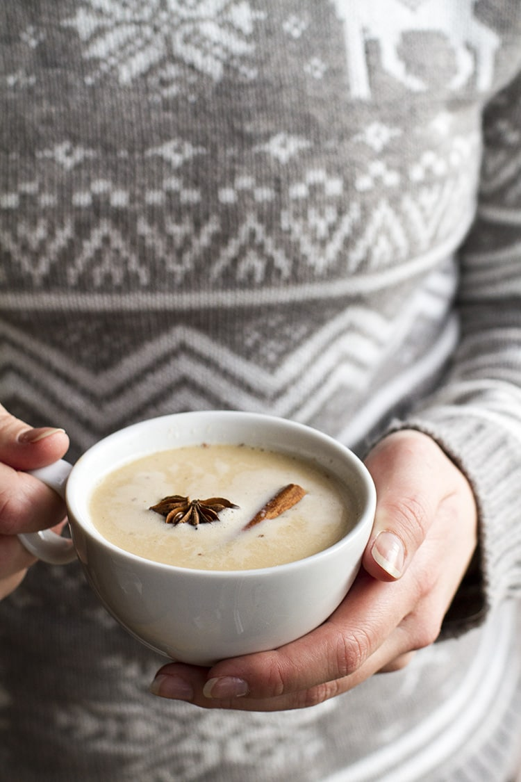 Person with grey knitted sweater holding a cup of warm eggnog white russian.