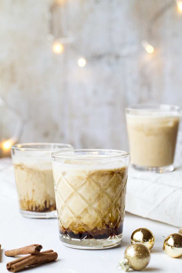 Three white russians with coffee at the bottom. Lights around.