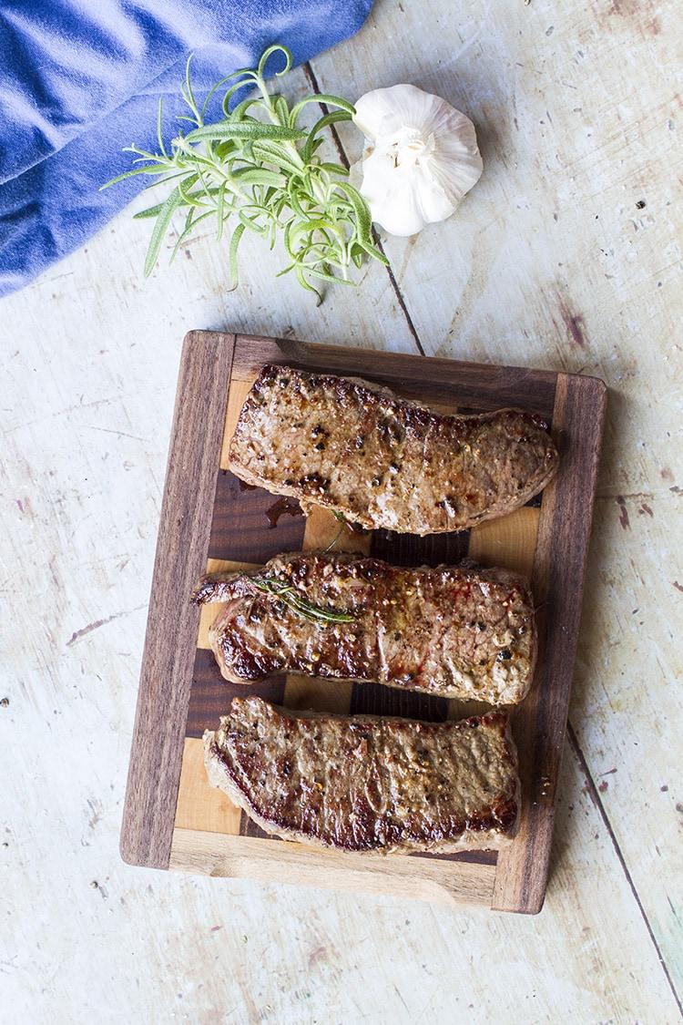 3 striploin steaks on a cutting board.