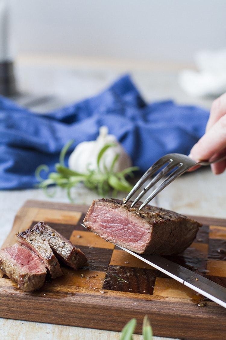 Knife and fork holding up a sliced medium-rare steak.
