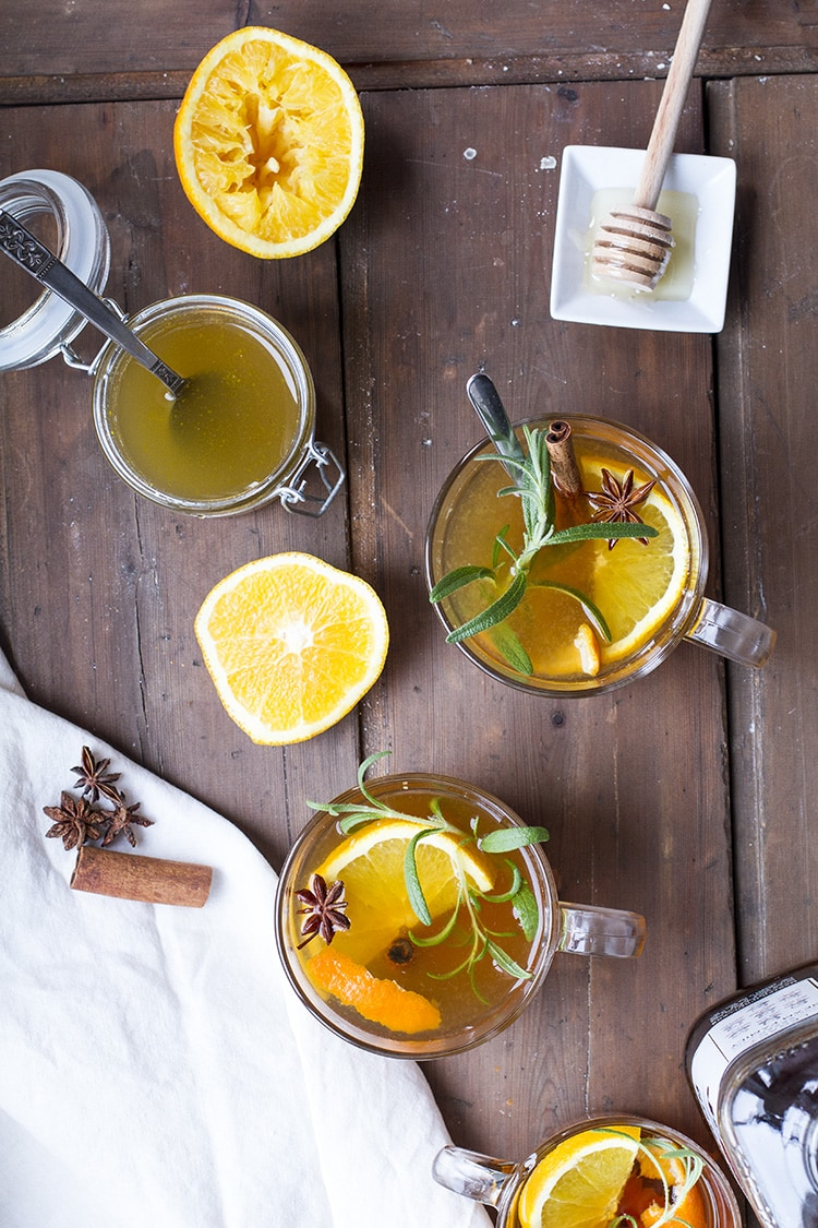 Three glass mugs with hot toddy, garnished with orange slices and rosemary.