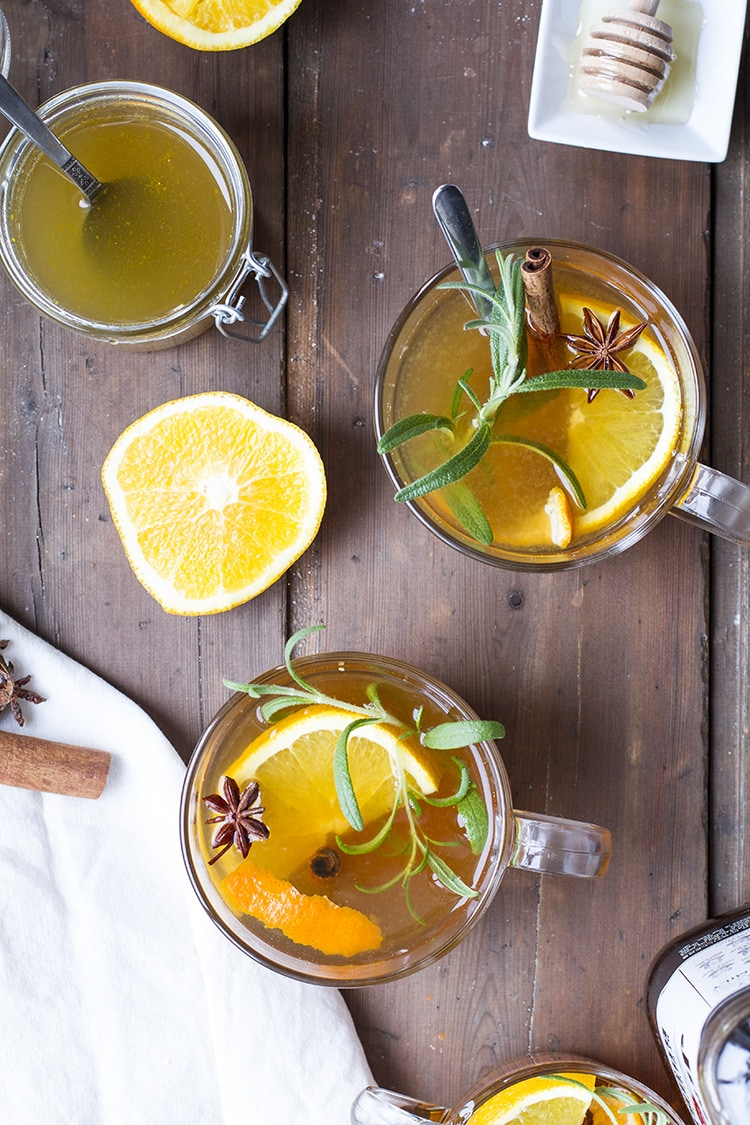 Two glass mugs with toddy, garnished with rosemary and orange wedges. Flat-lay.