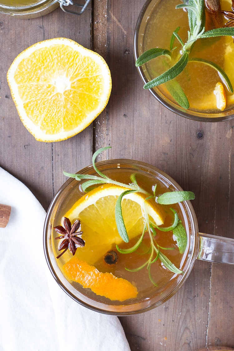 Close-up of a whiskey toddy seen from above, garnished with orange slice, fresh rosemary and star anise.