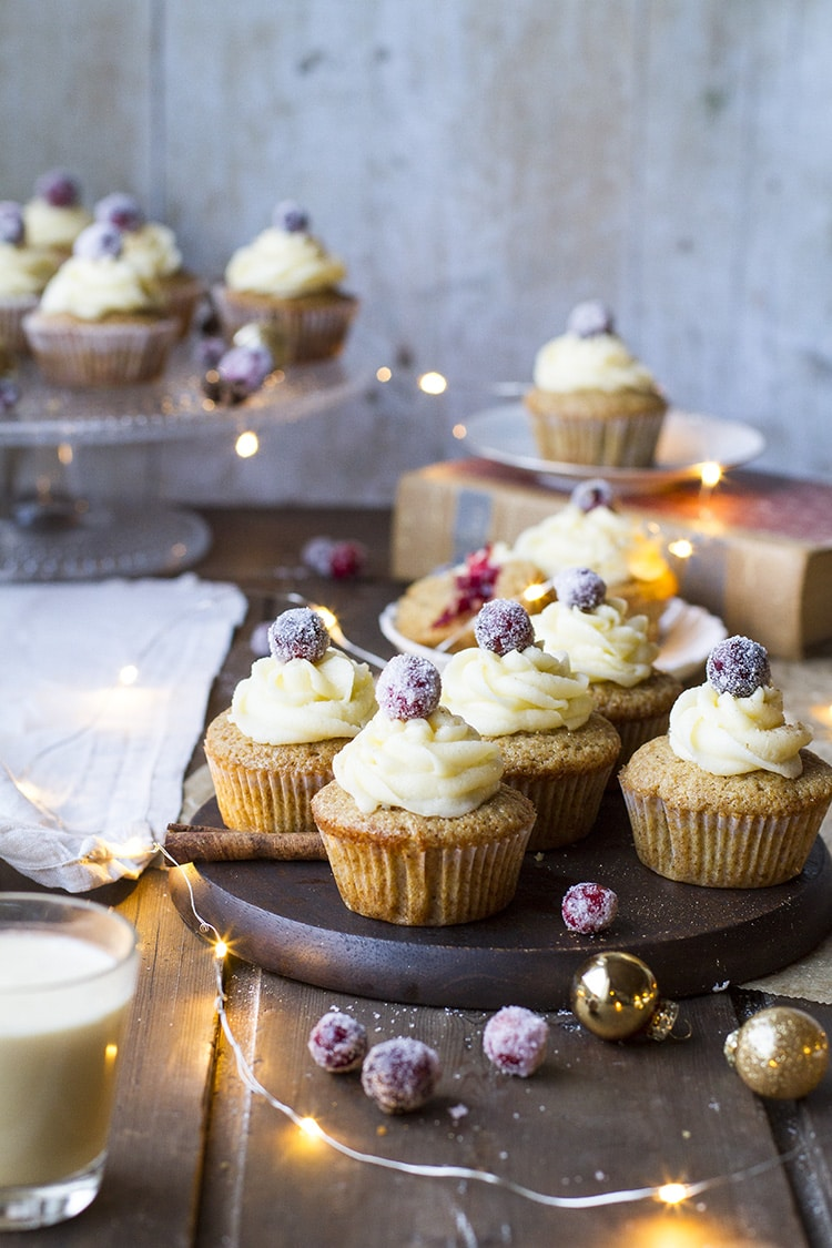 Gingerbread cupcakes with eggnog frosting and one sugared cranberry at the top.
