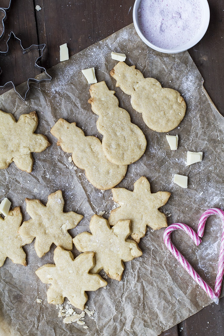 Undecorated snowmen and star shaped white chocolate cookies on a parchment paper.