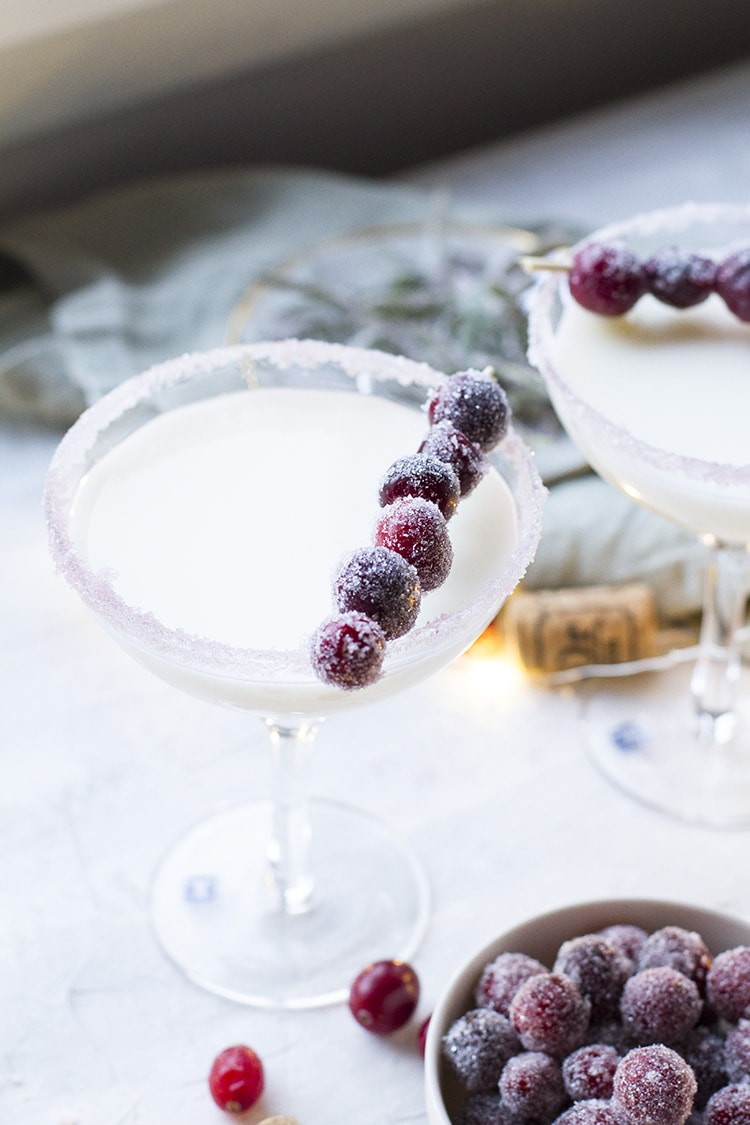 A coupe glass with a white cocktail and sugar frosted cranberries.