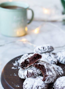 Chocolate crinkle cookies, some opened, on a wooden plate.